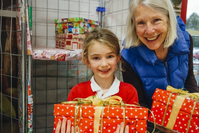 Little Girl And Her Grandmother Are Posing For The Camera With The Charity Christmas Box They Have Made.