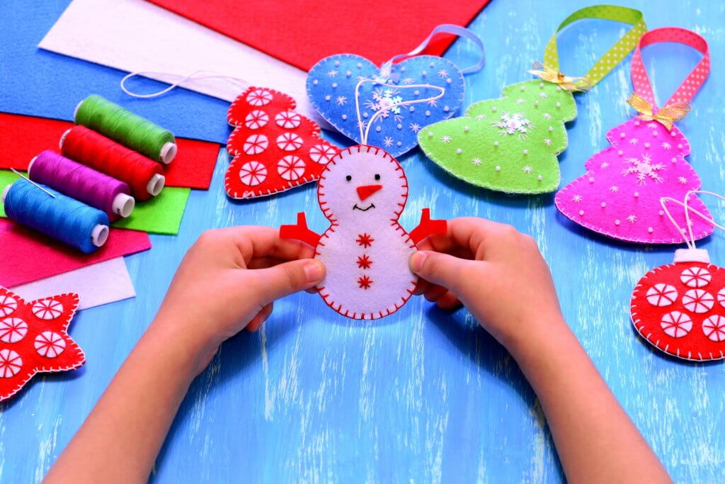 Child holds a felt snowman ornament in his hands. Christmas sewing crafts concept. Christmas tree, heart, star, snowman crafts, sewing kit, bright felt sheets on blue wooden background