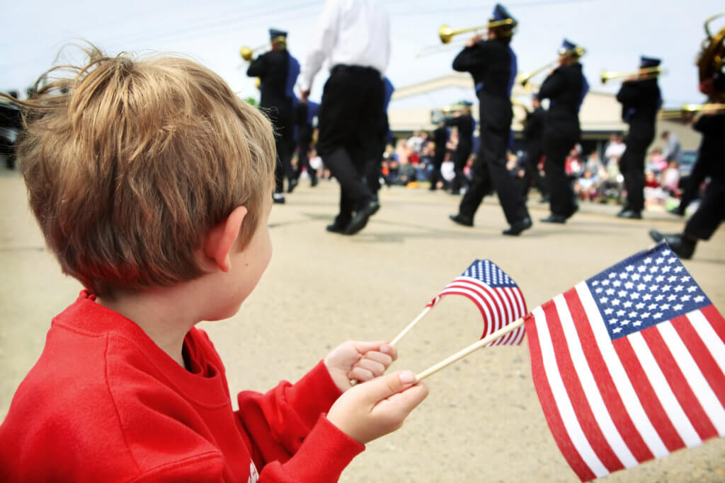 a young boy watching a parade while waving a couple of  US Flags