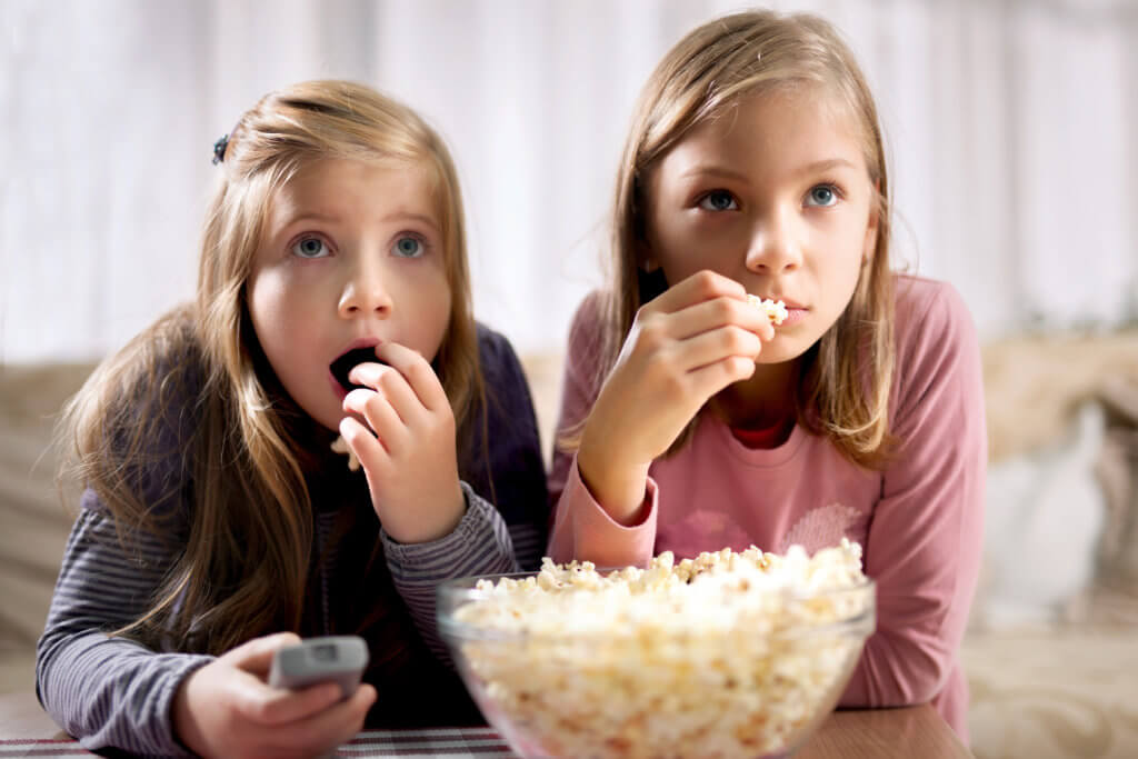 Two young beautiful girls  eating popcorn and watching movies
