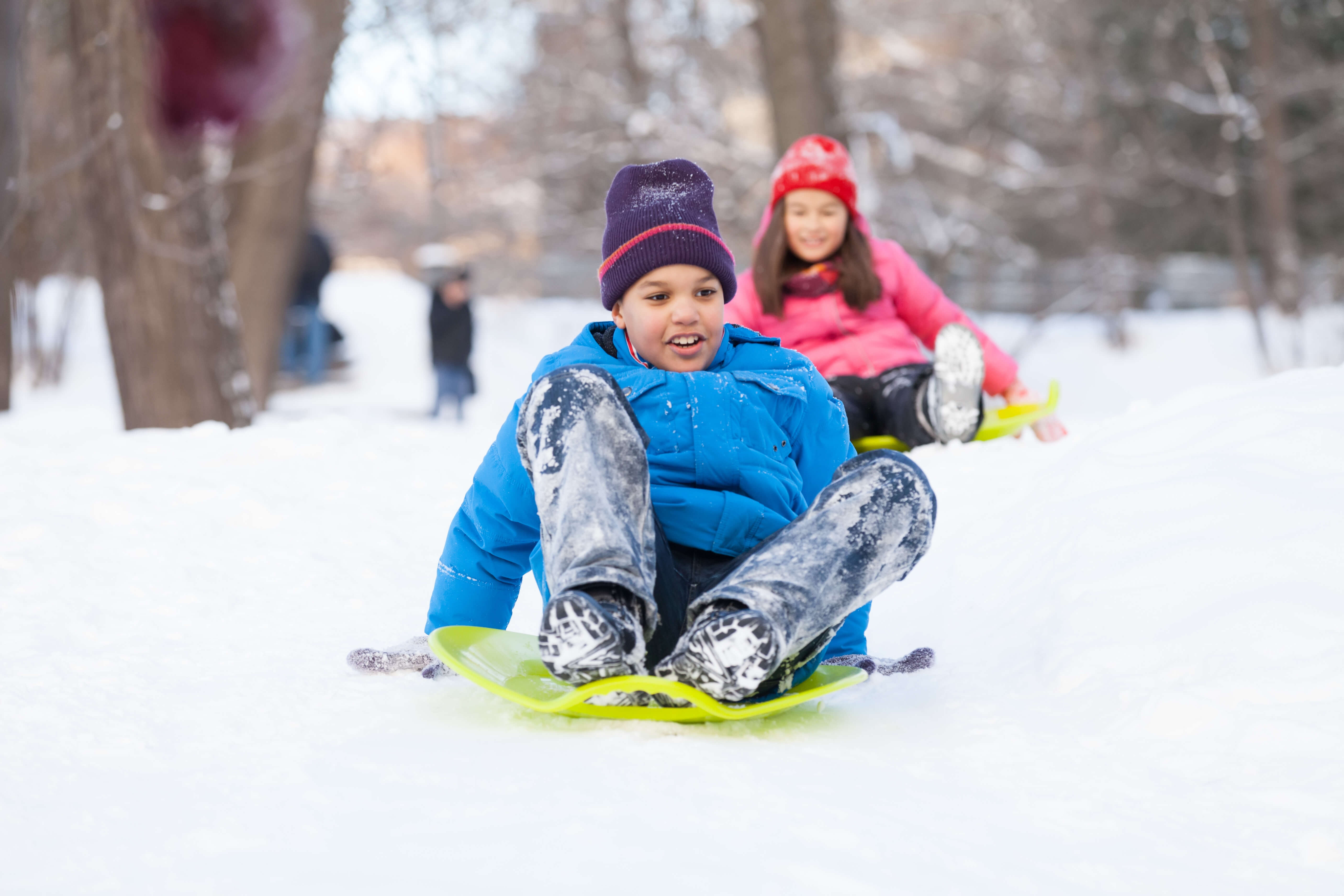 Boy And Girl Sliding On Sledges In Park. Two Children Sitting On Sledges And Speeding Down