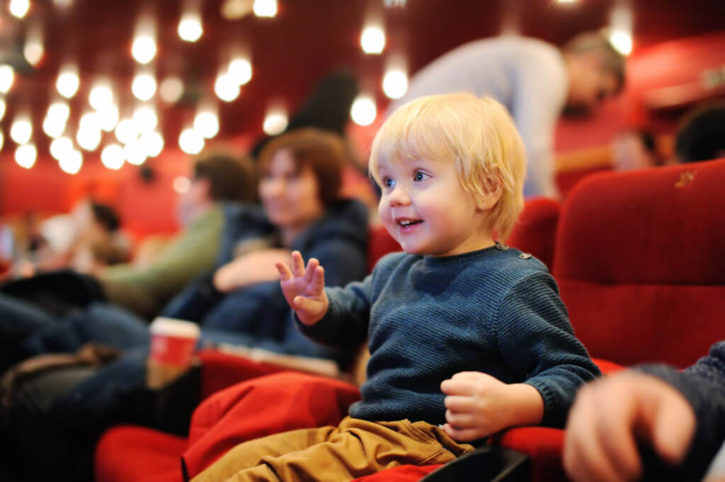 Cute toddler boy watching cartoon movie in the cinema. Leisure/entertainment for family with kids.