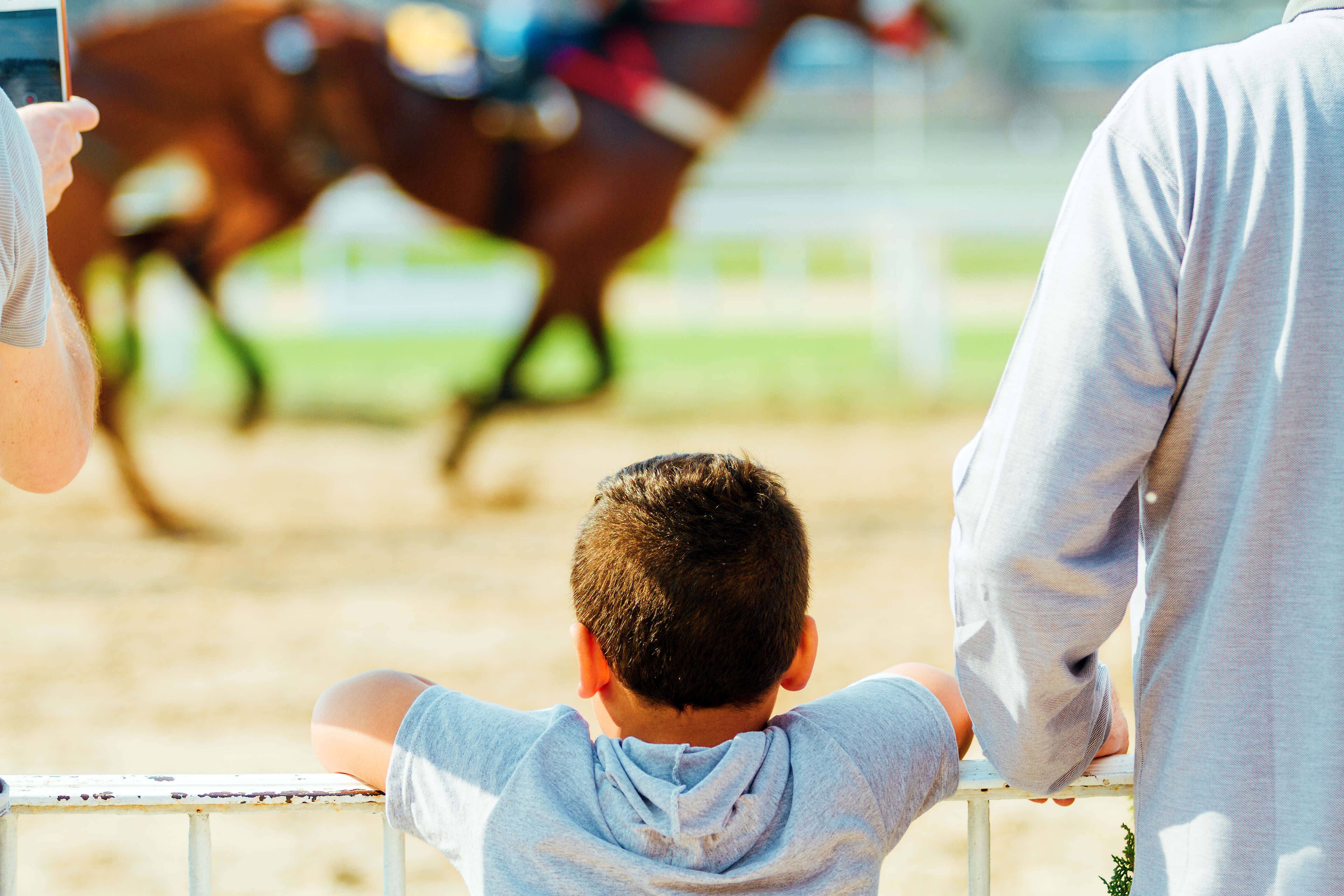 Child looking at a horse race next to an adult and horse on background