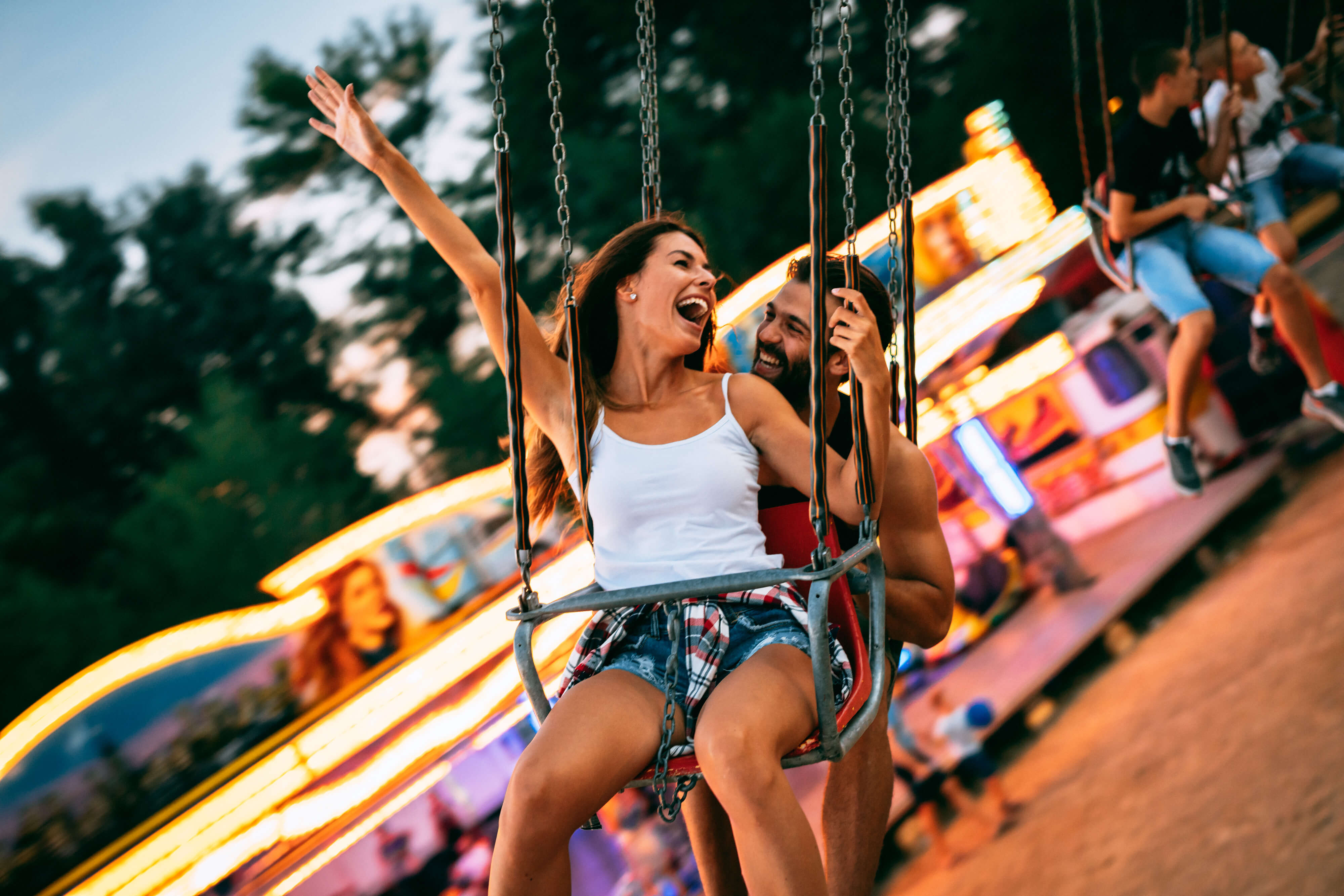 Young Couple Enjoying On The Swings