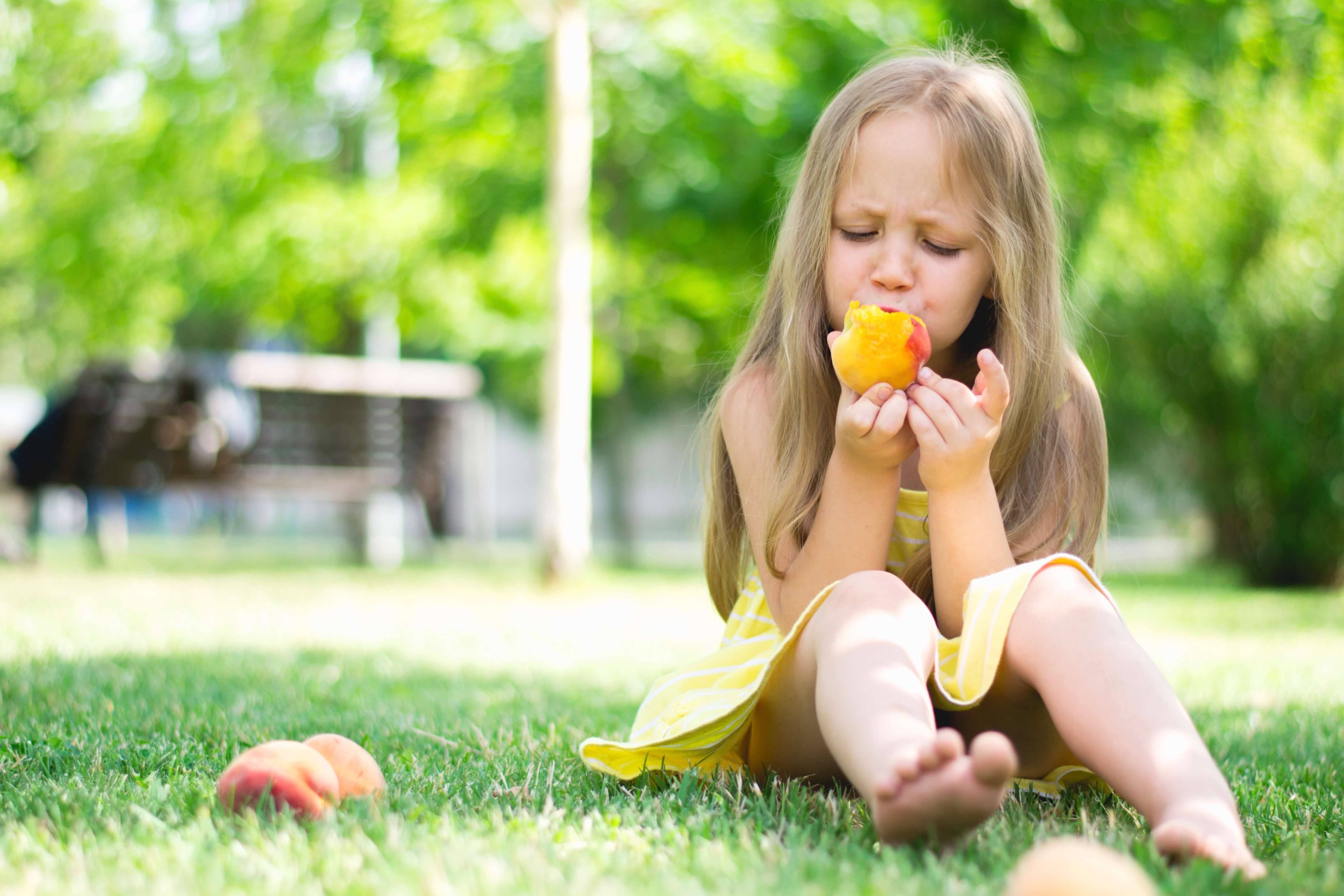 Little girl is eating peaches in the park