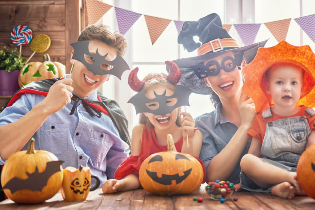 Mother, father and their daughters having fun at home. Happy family celebrating for Halloween. People wearing carnival costumes.