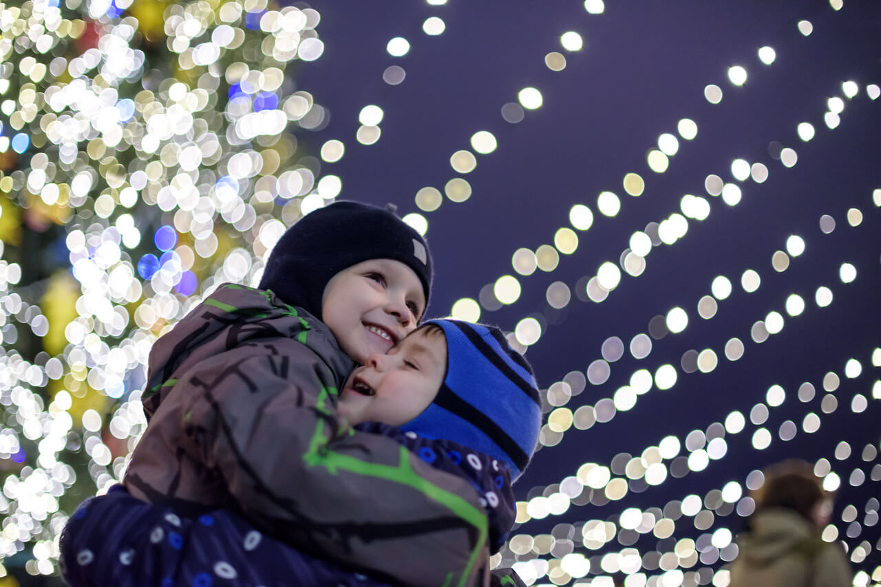 Family, Childhood, Season And People Concept - Happy Kids Brothers Boys In Winter Clothes Over Snow City Background With Xmas Lights Bokeh