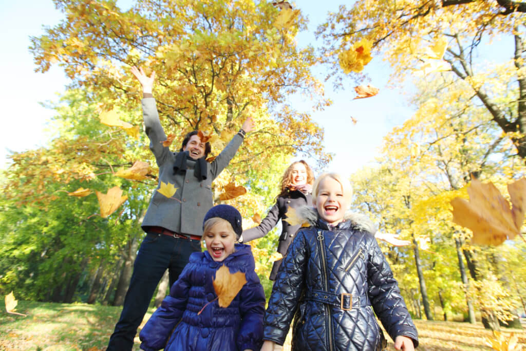 Happy family playing with autumn maple leaves in park