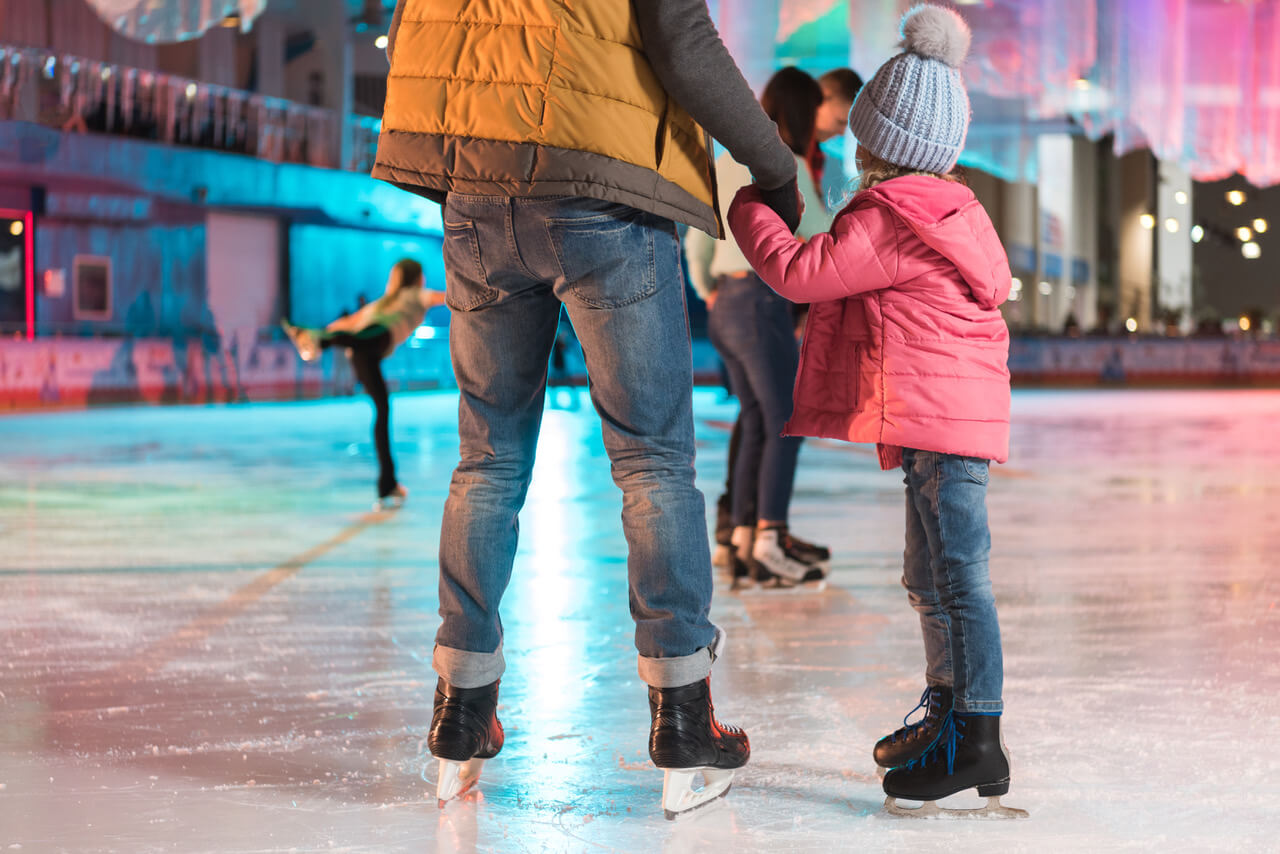 Cropped Shot Of Father And Daughter Holding Hands While Standing Together On Skating Rink