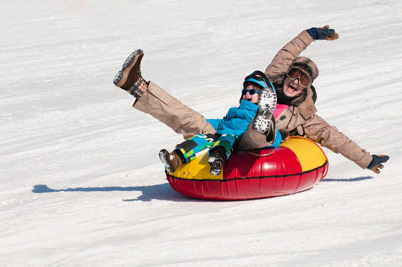 Young Woman And Little Boy Having Fun In Snow Tube
