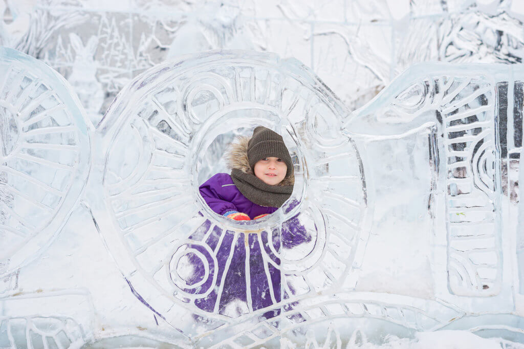 Boy hiding behind an ice sculpture. Patterned wall of ice. Winter park