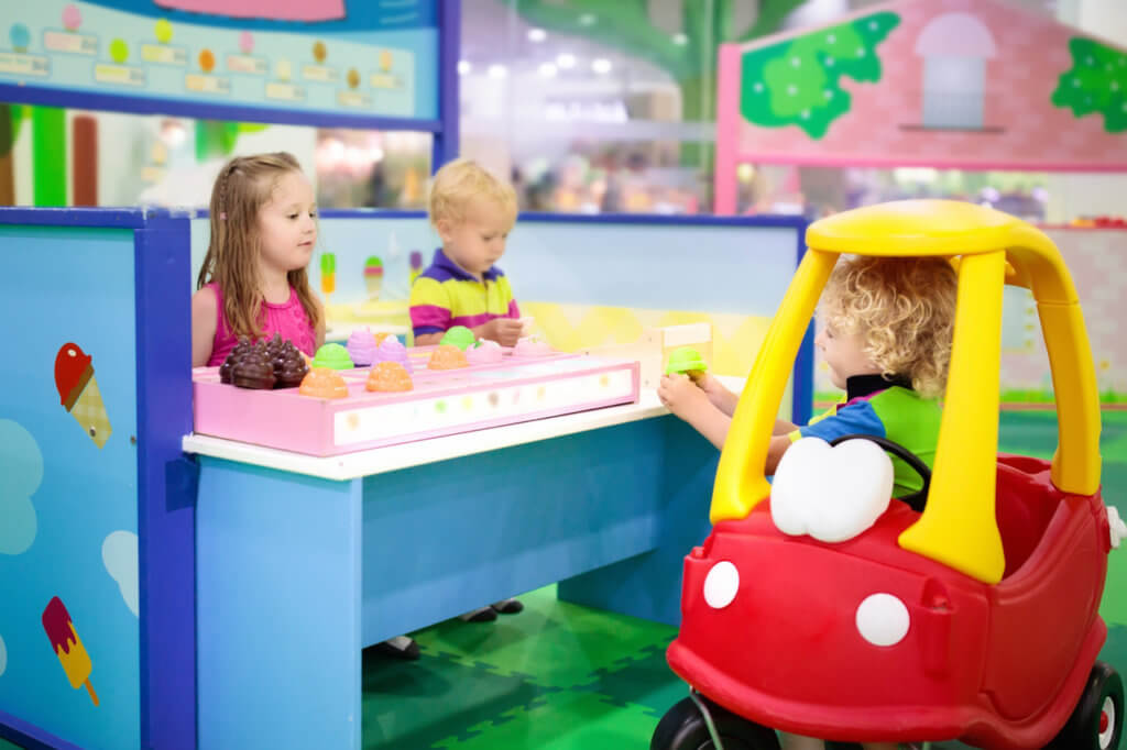 Child playing in toy shop or restaurant. Educational toys and role game for kids. Kindergarten or preschool play room. Toddler kid at day care playground. Grocery store or supermarket for children.
