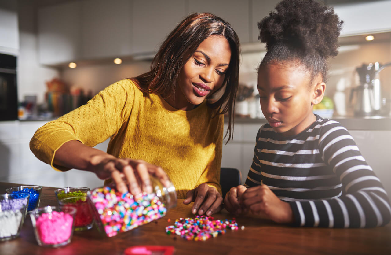Attractive African female parent pouring colorful beads from jar on wooden table for child sitting in kitchen