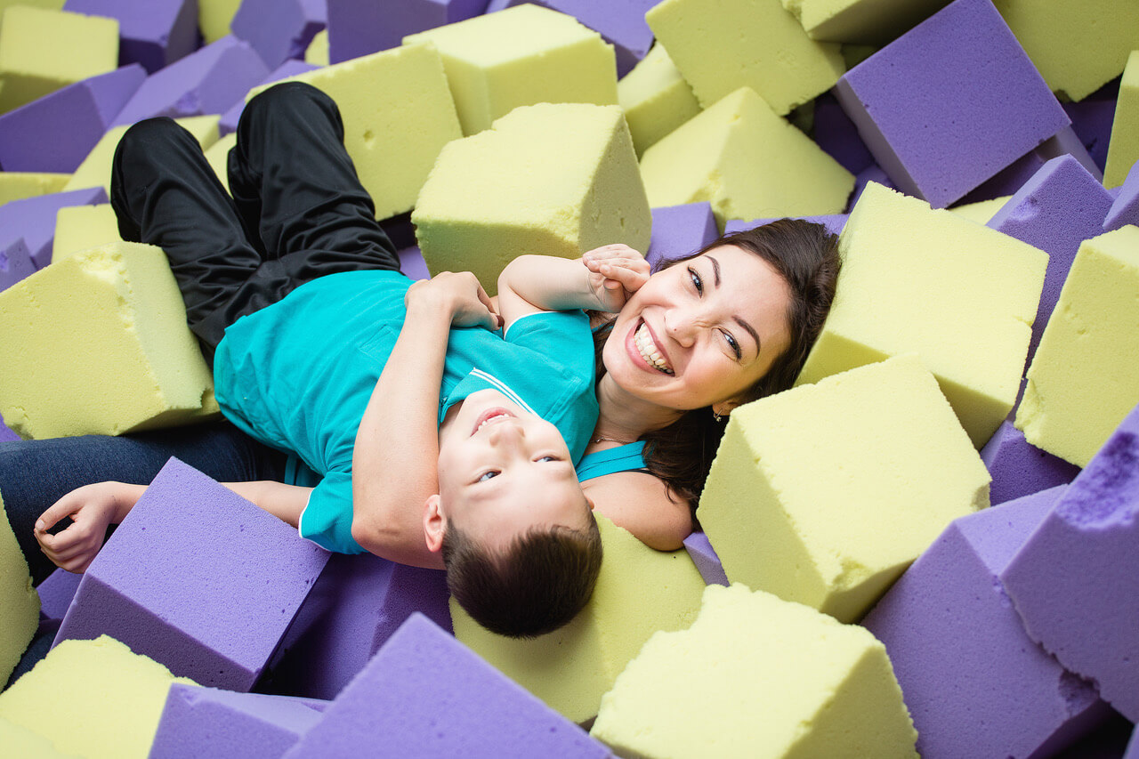 Asian Mother And Her Son Playing Blocks At Indoor Playground.