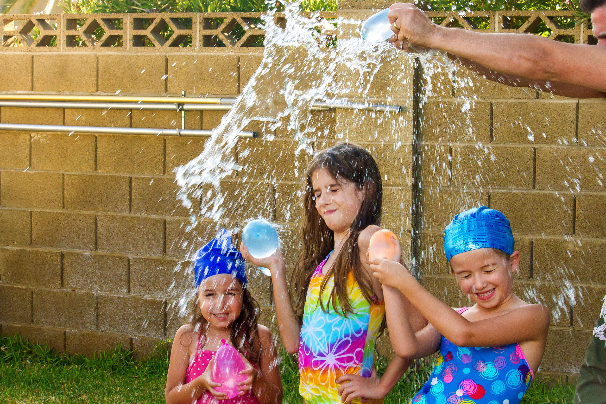 The arms of a father break a blue water balloon over the heads of his three daughters. The girls are wearing bathing suits and two of them have swim caps on.