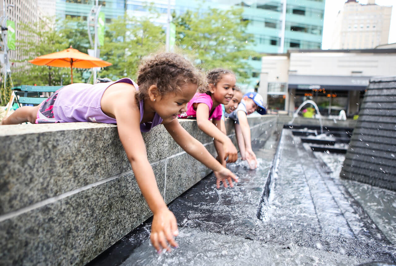 Children Playing In A City Fountain. Shallow Focus On Girls Face.