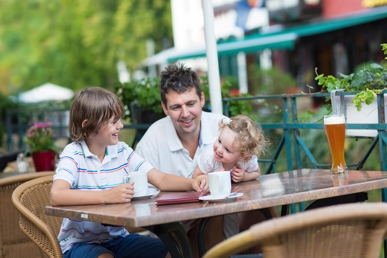Beautiful young family – a father and two of his children, baby daughter and school boy – enjoying a meal in an outside cafe on a sunny terrace
