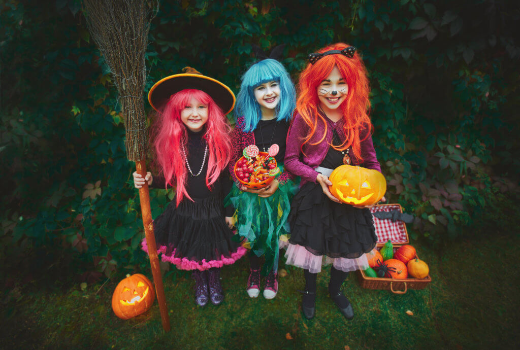 Three happy witches asking for treat on Halloween evening