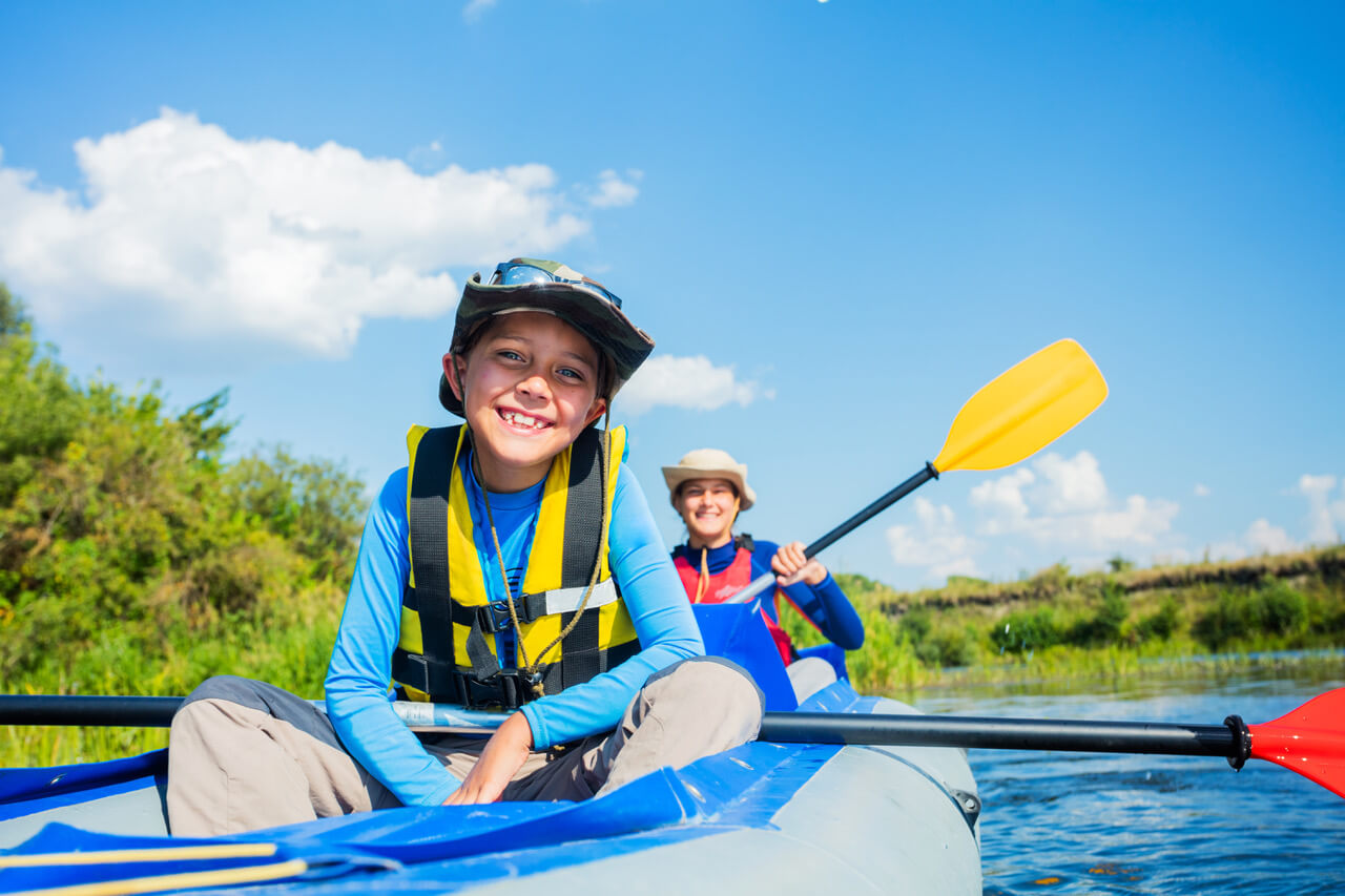 Happy boy kayaking with his sister on the river. Active boy having fun enjoying adventurous experience with kayak on a sunny day during summer vacation
