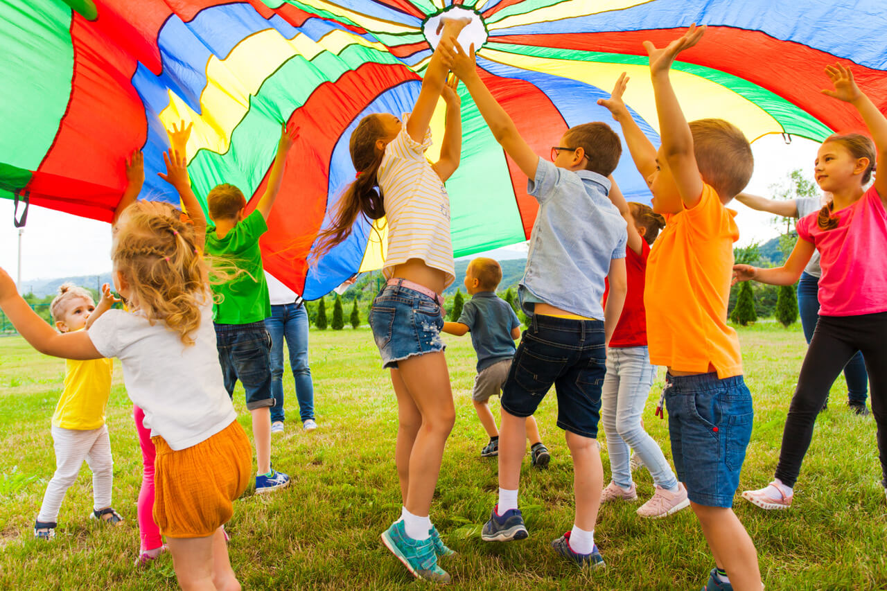 Joyful Friends Jumping And Bouncing, Trying To Catch Flying Rainbow Parachute