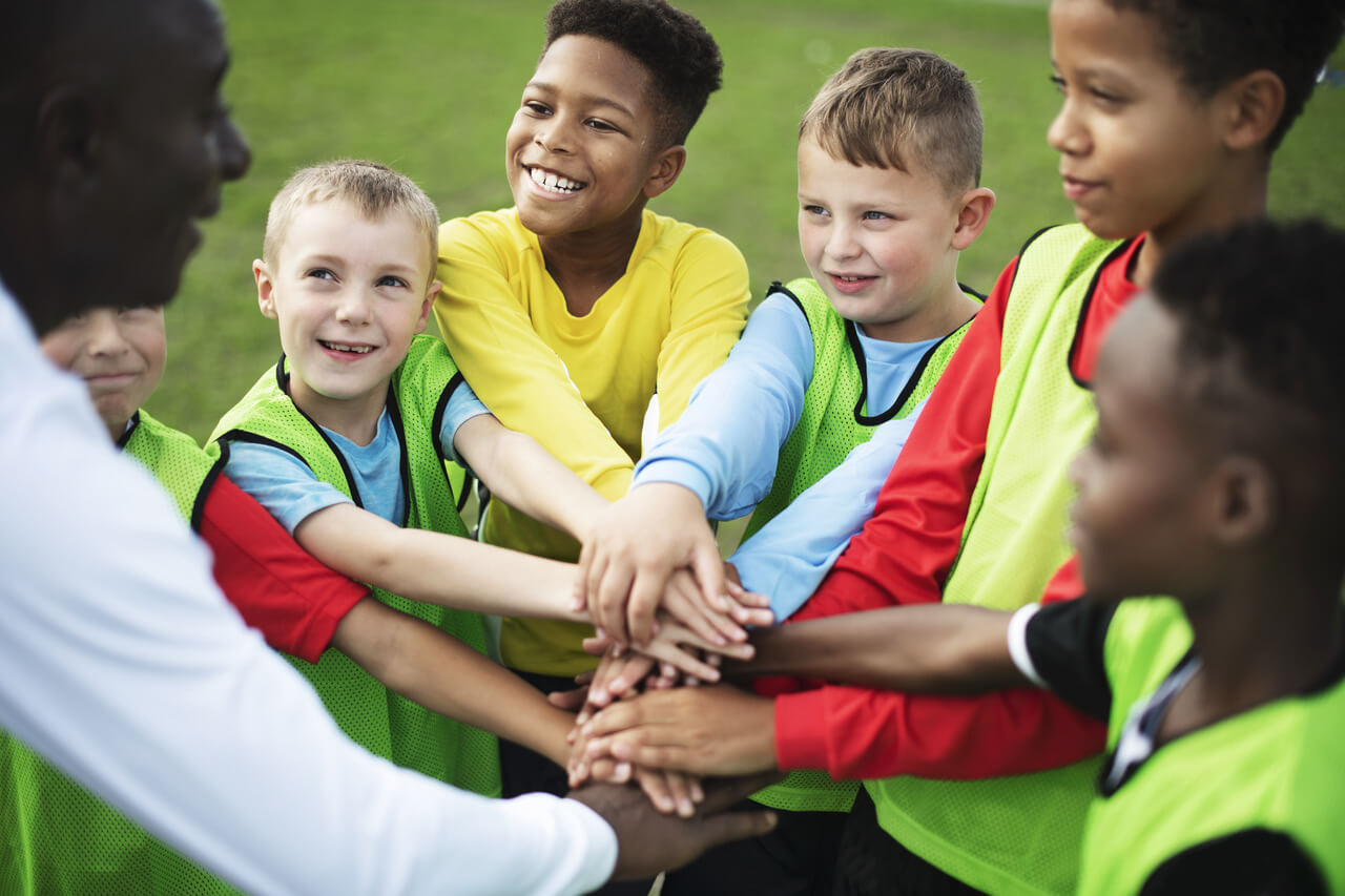 Junior football team stacking hands before a match