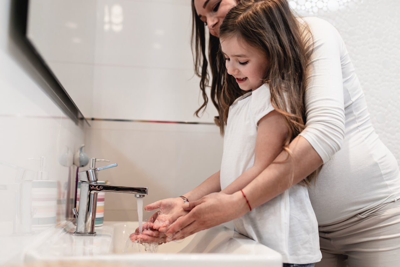 Caring Pregnant Mother And  Her Cute Little Daughter Washing Their Hands In Bathroom.