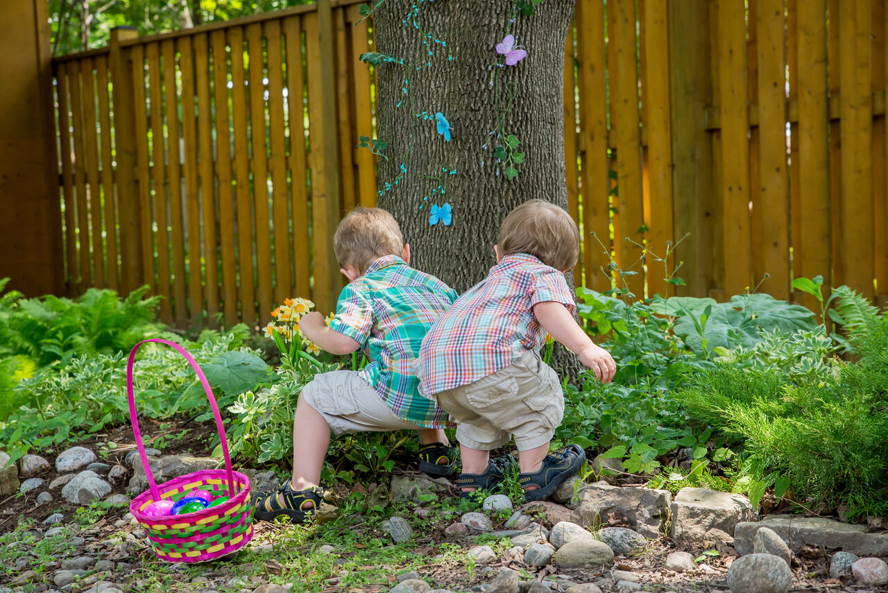 A basket full of colorful eggs sits beside two boys finding eggs during an Easter egg hunt outside in a beautiful garden in the spring. Part of a series.