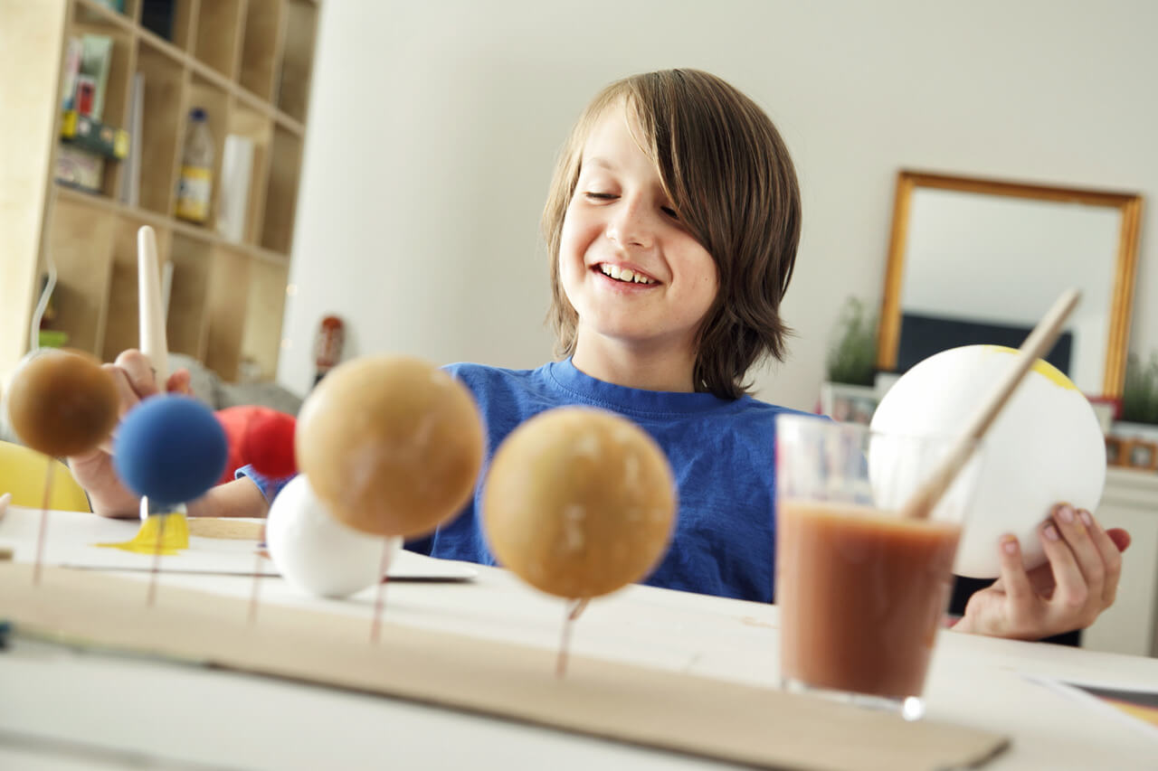 Happy School Boy Making A Solar System For A School Science Project At Home