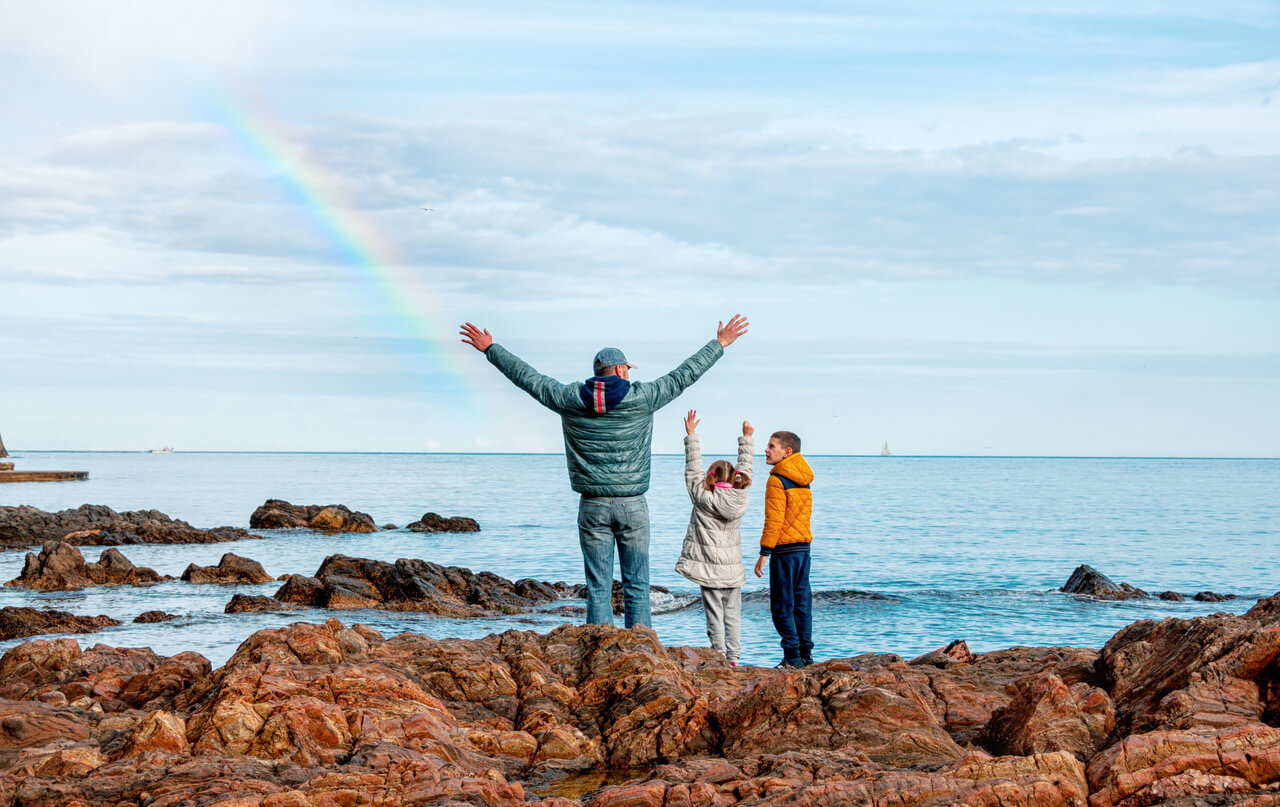 Children With Father Near The Sea Are Happy With The Rainbow. Concept Of A Happy Family.