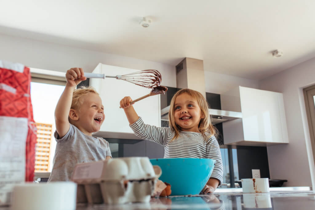 Cute little boy and girl fighting with whisk and spatula while mixing batter in a bowl. Siblings enjoying baking in home kitchen.