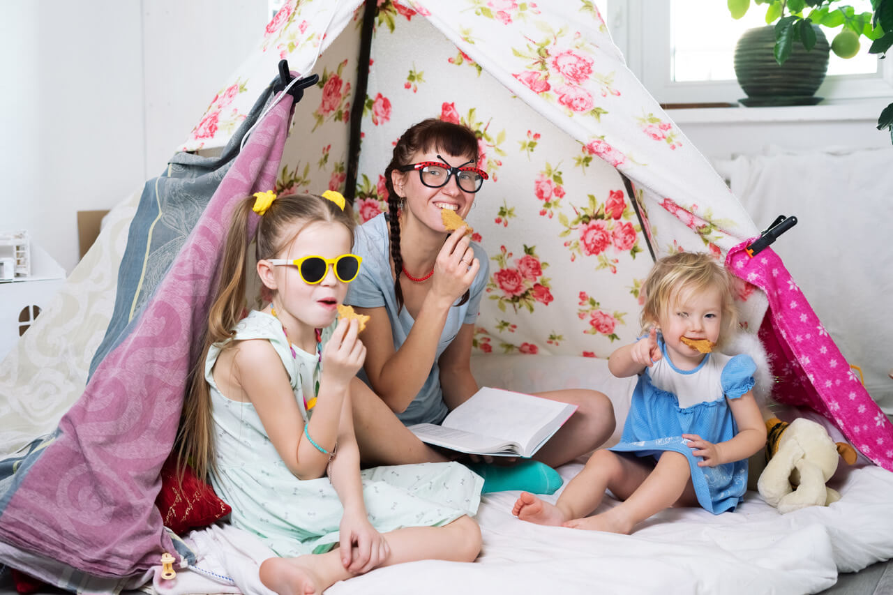 Family Time: Mom And Some Of The Sisters' Children Play At Home In A Children's Homemade Tent. Portrait.