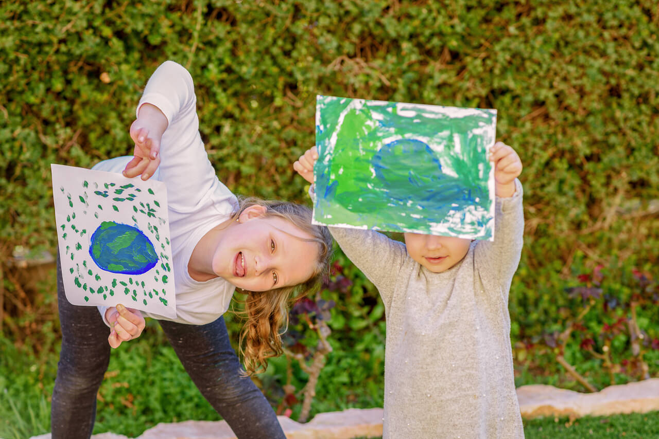 Portrait Of The Two Cute Little Girls Holding The Drawing Earth Globe. Children Draw A Picture Of Earth. GDPR Concept.