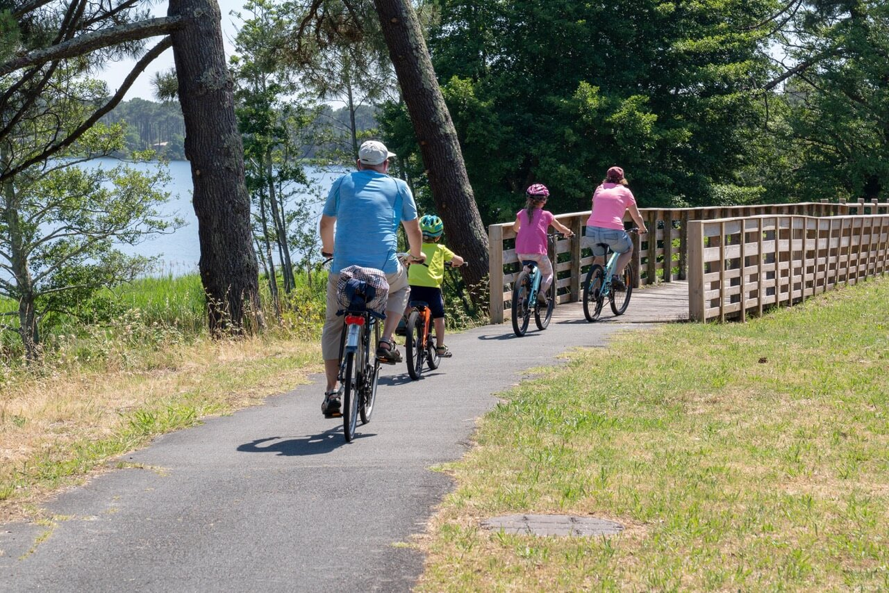 Tourist Family On Bike Ride In Lacanau Lake Bridge