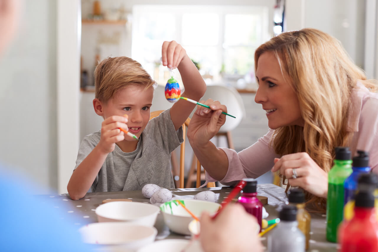 Mother With Son Sitting At Table Decorating Eggs For Easter At Home