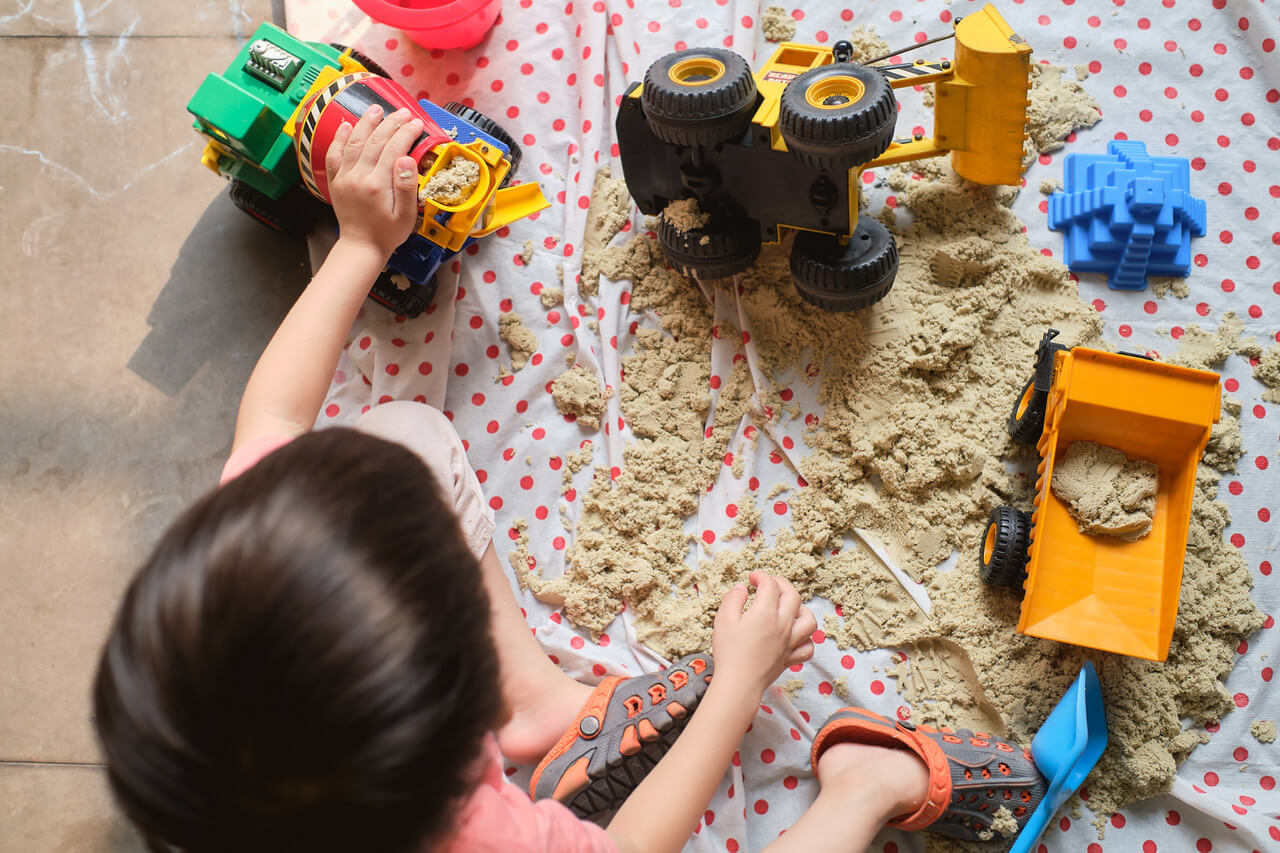 Bird Eye View Of Toddler Boy Playing With Kinetic Sand Alone At Home, Child Playing With Toy Construction Machinery, Fine Motor Skills Development, Montessori Education, Creative Play For Kids Concept