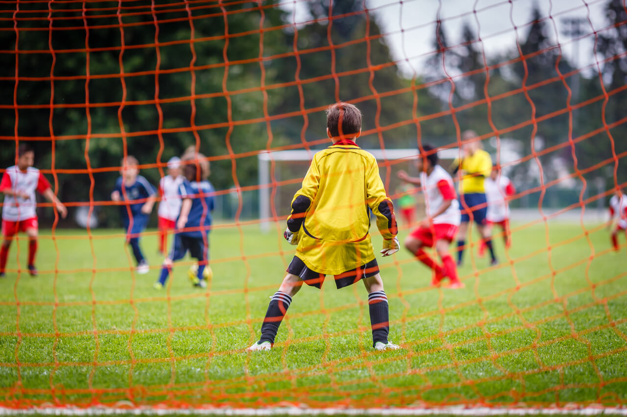 Young soccer goalie defending the net in the rain