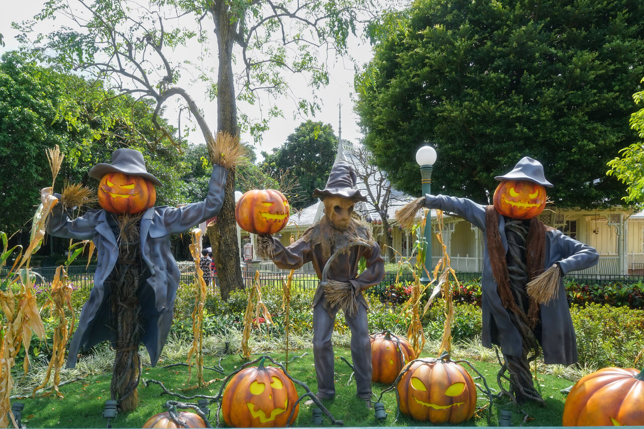 Scarecrow And Halloween Pumpkin Head Jack O Lantern Statues For Halloween Decoration Theme In An Outdoor Garden, Scary Pumpkins On The Ground. Toned Photo, Dark Tone For Halloween Concept