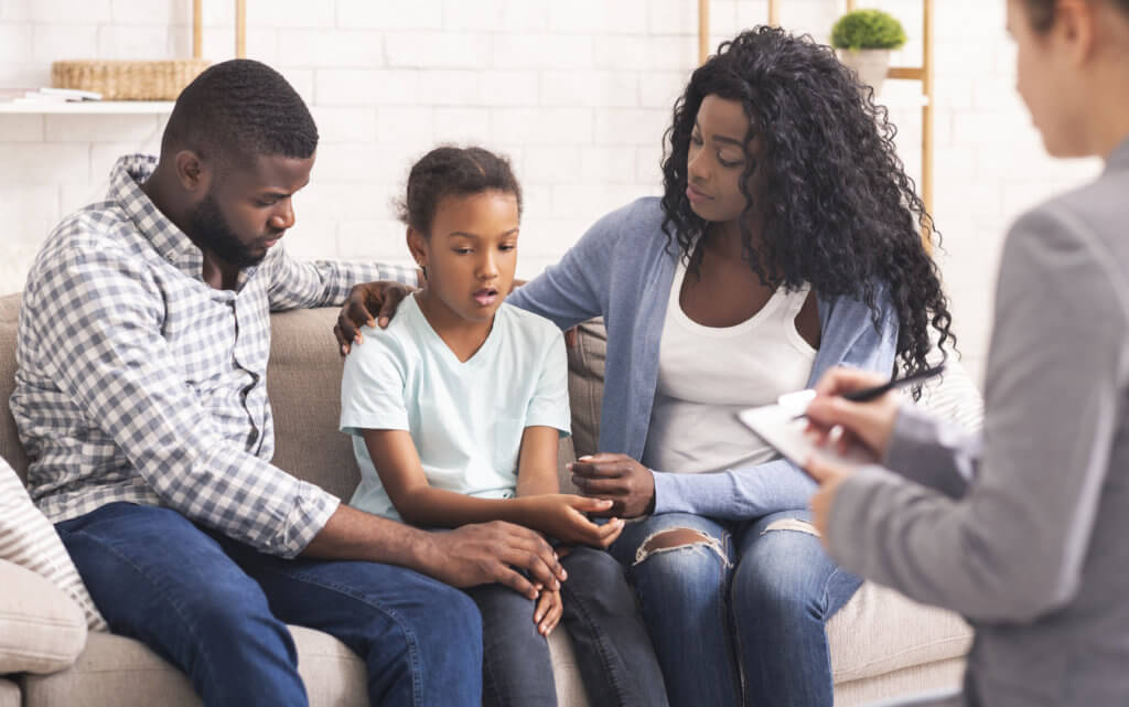 Bipolar Disorder In Children Concept. Little african american girl and her parents at reception of psychologist, kid sharing her feelings with doctor