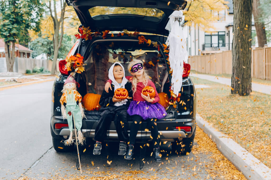 Trick or trunk. Children celebrating Halloween in trunk of car. Boy and girl with red pumpkins celebrating traditional October holiday outdoor. Social distance during coronavirus covid-19.