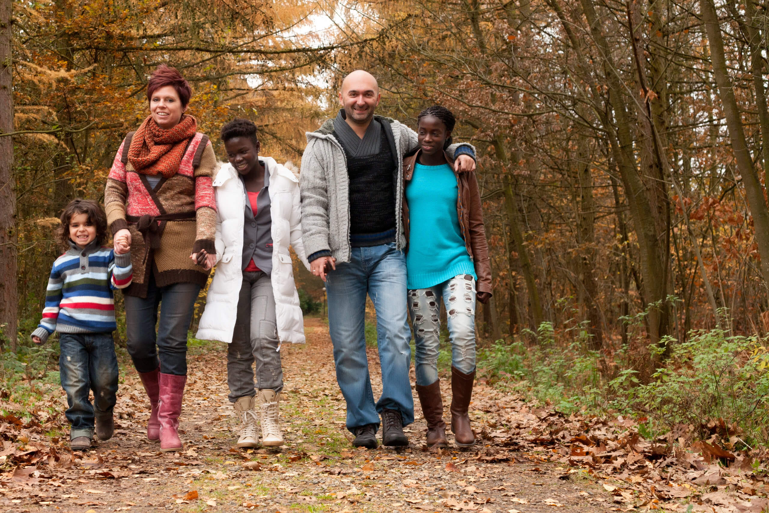 Happy family with foster children in the forest